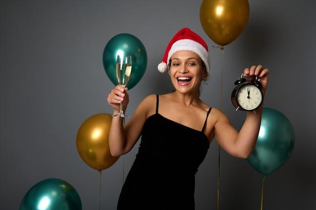 Mooie vrouw in santa carnaval hoed glimlacht brede glimlach poseren tegen glanzende lucht ballonnen op grijze achtergrond met wekker en champagne glas in handen, kopieer advertentieruimte. kerstmis, gelukkig nieuwjaar