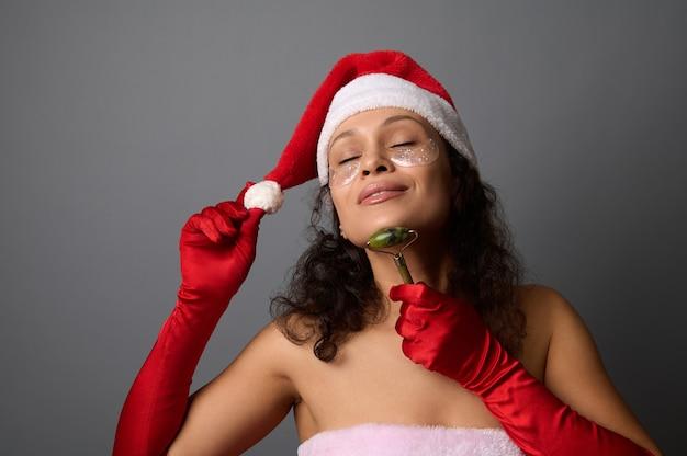 Mooie vrouw in santa carnaval kleding, met cosmetische patches onder de ogen, geniet van het opheffen van lymfedrainage gezichtsmassage met jade roller stimulator. ruimte kopiëren voor kerstadvertentie voor beauty spa salon
