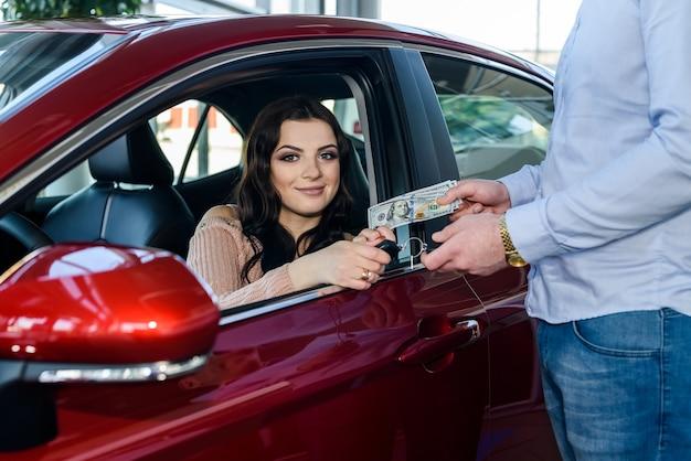 Mooie vrouw in showroom die geld geeft en sleutels uit de auto haalt