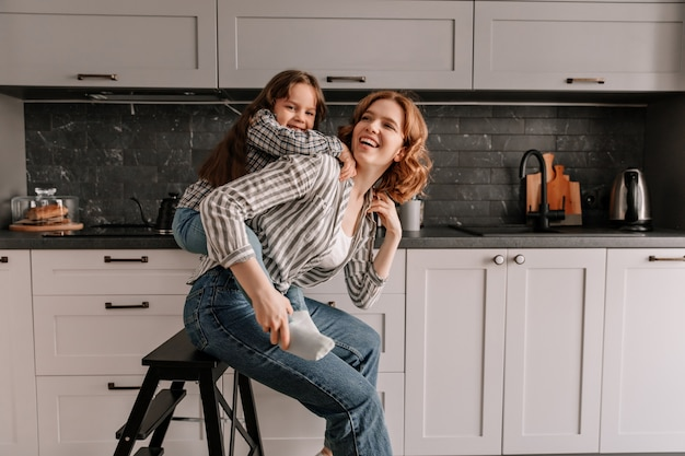 Mooie vrouw in spijkerbroek zit op stoel in de keuken terwijl haar dochter haar van achteren koestert.