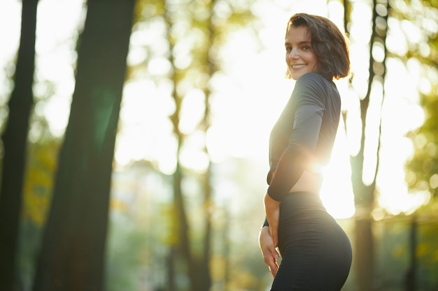 Mooie vrouw in sport outfit poseren in het park