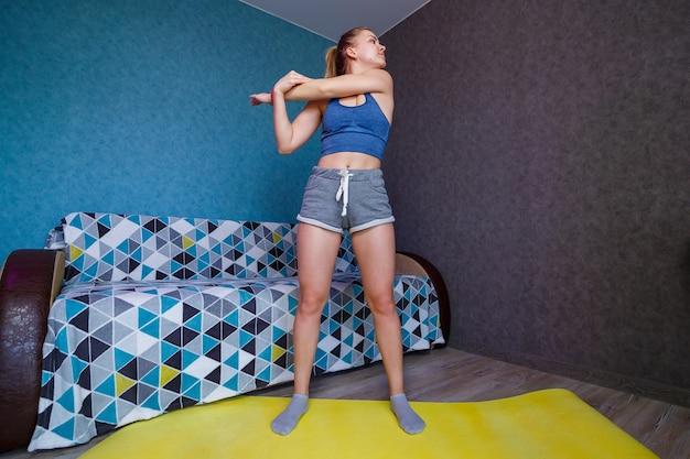 Mooie vrouw in sportkleding, korte broek en een beha die in een pose staat, oefeningen, aantrekkelijk meisje dat yoga beoefent, thuis of in een moderne yogastudio traint, lichaam strekken
