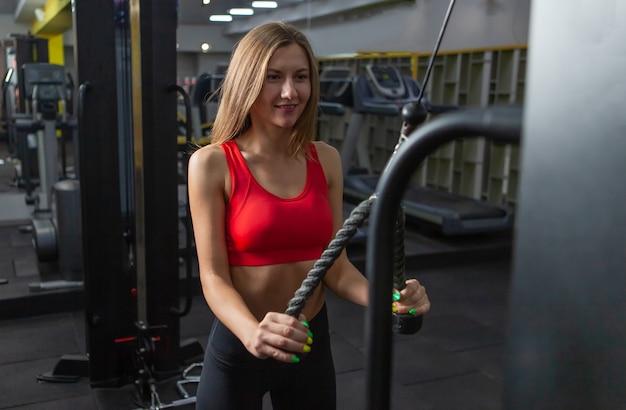 Mooie vrouw in sportkleding oefening met kabelgewichtmachine in moderne sportschool.