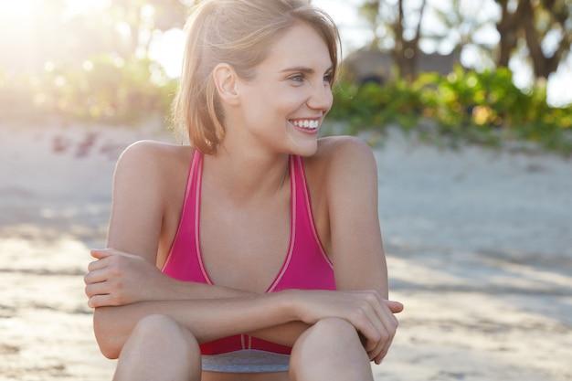 Mooie vrouw in sportkleding op strand