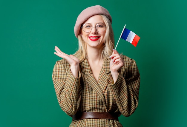 Mooie vrouw in stijljasje en hoed met franse vlag op groene muur