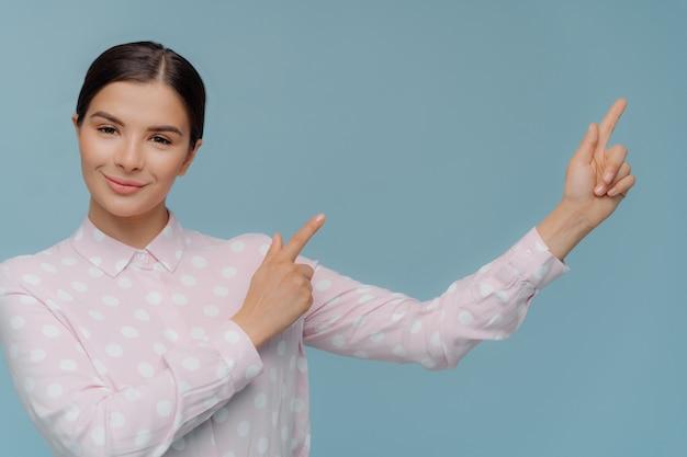 Mooie vrouw in stijlvolle kleding wijst weg in lege linkerhoek