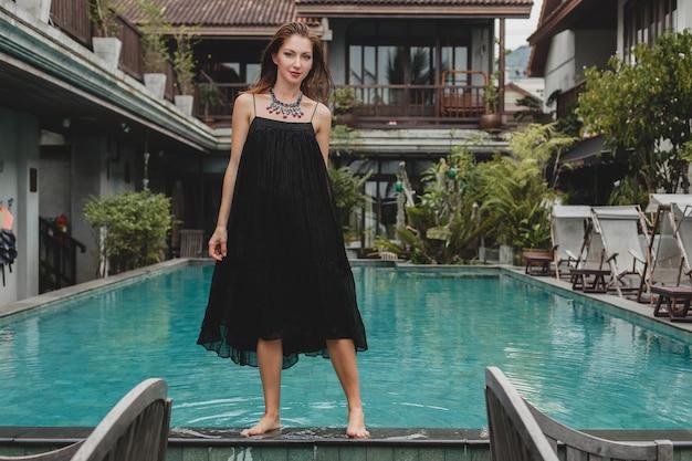 Mooie vrouw in stijlvolle lange zwarte jurk poseren bij tropische villa zwembad, elegante zomerstijl, vakantie, modetrend, blootsvoets lopen