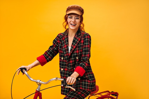 Mooie vrouw in stijlvolle outfit fietst op oranje muur