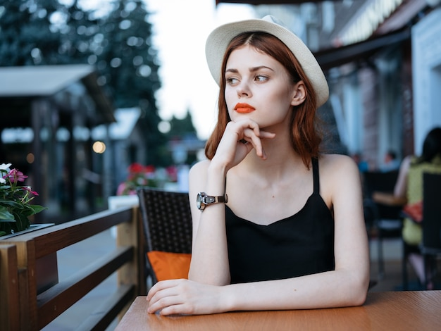 Mooie vrouw in straat café model restaurant emoties hoed jurk