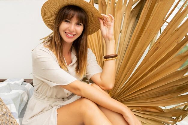 Mooie vrouw in strooien hoed en linnen jurk poseren op witte achtergrond en droog palmblad.