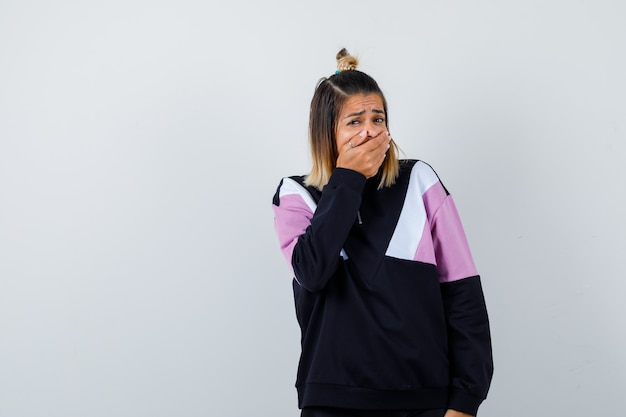 Mooie vrouw in sweatshirt sluit mond met hand en kijkt geschokt