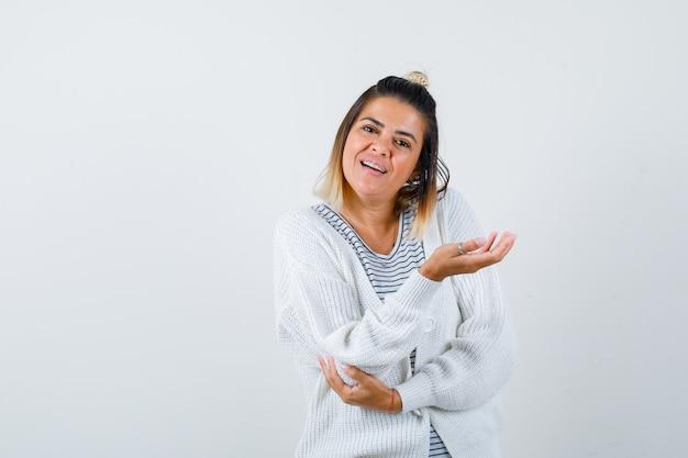 Mooie vrouw in t-shirt, vest spreidt handpalm opzij en kijkt verward