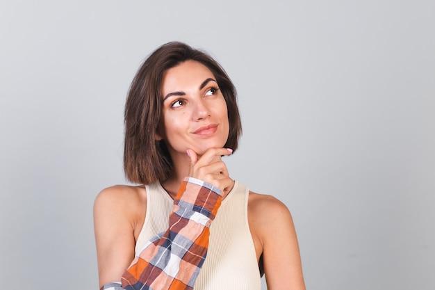 Mooie vrouw in top en geruit hemd op grijze muur met make-up die attent glimlacht en opzij kijkt