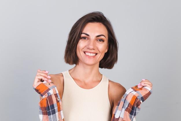 Mooie vrouw in top en geruit hemd op grijze muur met make-up positieve zelfverzekerde glimlach, gelukkige emoties