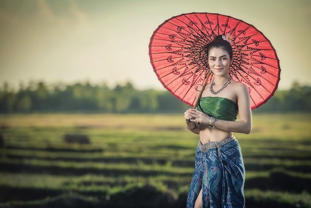 Mooie vrouw in traditioneel kledingskostuum, aziatische vrouw die typische thaise kleding draagt