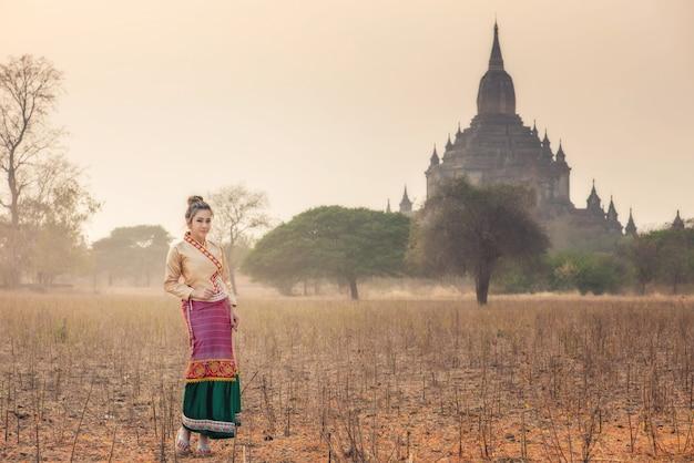 Mooie vrouw in traditionele klederdracht van myanmar poseren in het veld