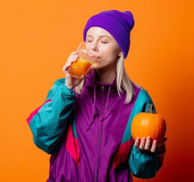 Mooie vrouw in trainingspak uit de jaren 90 met pompoensap op sinaasappel