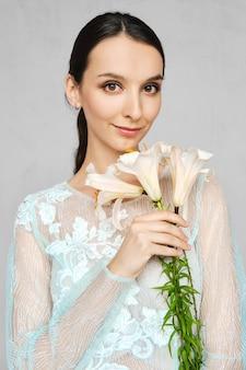 Mooie vrouw in transparante bleke jurk met kant poseren met bloemen in de hand