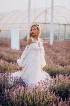 Mooie vrouw in trouwjurk in lavendelveld Gratis Foto