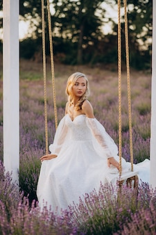 Mooie vrouw in trouwjurk in lavendelveld