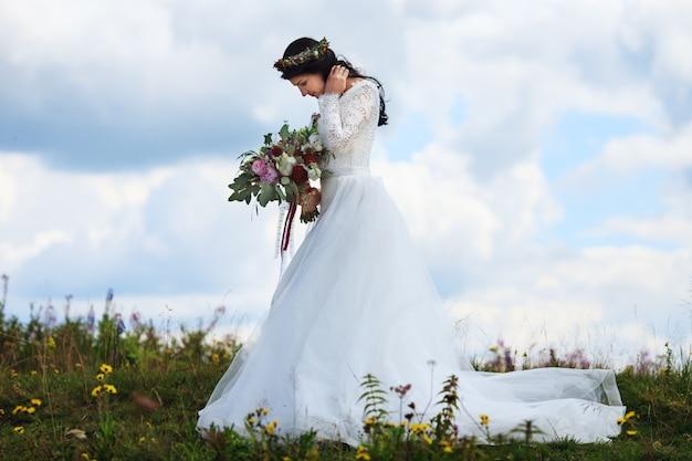 Mooie vrouw in trouwjurk poseren in de bergen. pre-wedding fotoshoot