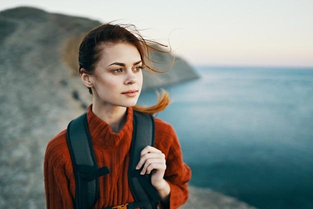 Mooie vrouw in trui met rugzak op haar rug glimlach toerisme zee natuur