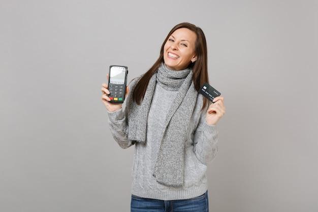 Mooie vrouw in trui, sjaal houdt draadloze moderne bankbetaalterminal vast om te verwerken, creditcardbetalingen te verwerven die op grijze achtergrond worden geïsoleerd. lifestyle, oprechte emoties van mensen, concept van het koude seizoen.