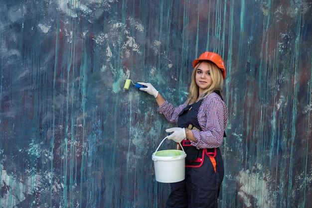 Mooie vrouw in uniform en helm met verf en roller die zich klaarmaakt om het huis te renoveren. bouwvakker.