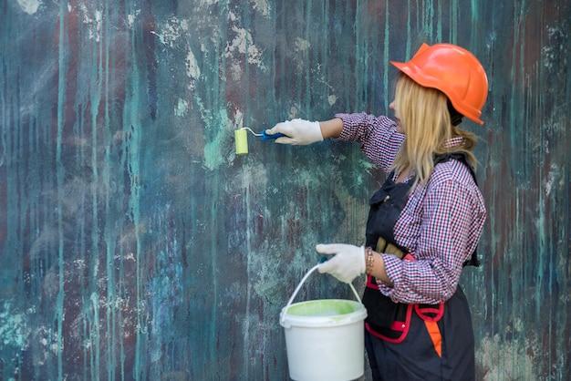 Mooie vrouw in uniform en helm met verf en roller klaar om huis te renoveren
