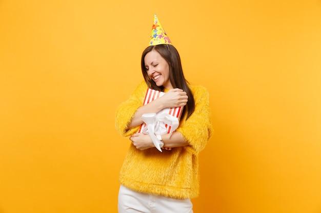 Mooie vrouw in verjaardagshoed knuffelen met rode doos met cadeau, aanwezig vieren, genieten van vakantie geïsoleerd op felgele achtergrond. mensen oprechte emoties, lifestyle concept. reclame gebied.
