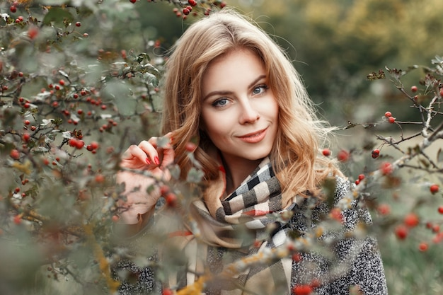 Mooie vrouw in vintage gebreide sjaal poseren in de buurt van een boom met bessen