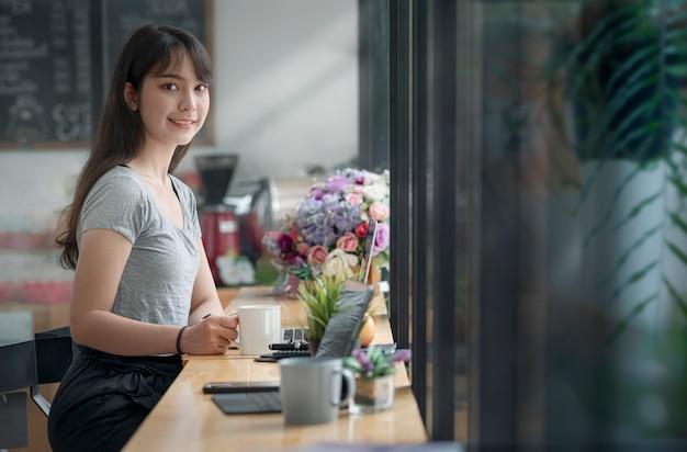 Mooie vrouw in vrijetijdskleding met mok zittend aan de balie in co-werkruimte met geluk. glimlachend en kijkend naar de camera.