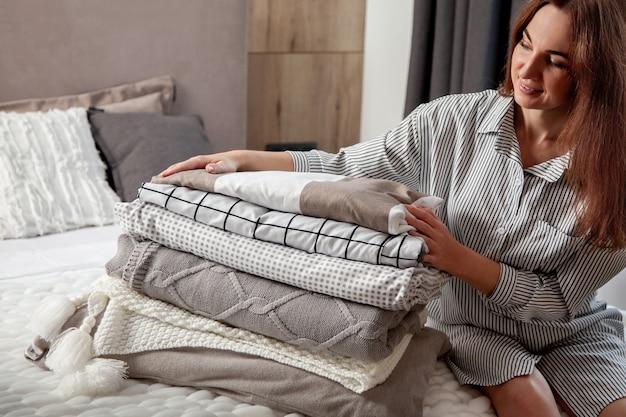 Mooie vrouw in winter dikke warme mantel zit en netjes opklapbaar beddengoed en witte badhanddoeken. schoon wasgoed organiseren en sorteren. biologisch en natuurlijk katoenen textiel. vervaardiging.