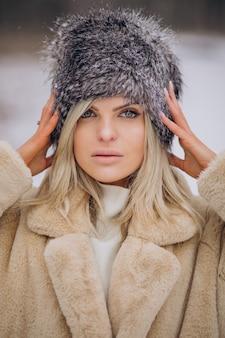 Mooie vrouw in winterjas wandelen in park vol sneeuw sn
