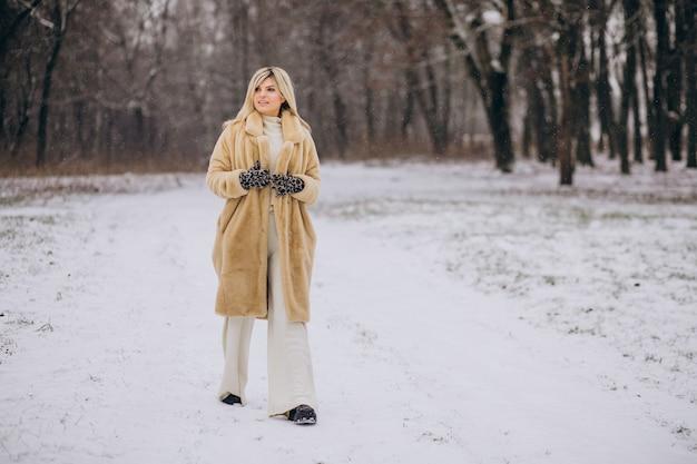 Mooie vrouw in winterjas wandelen in park vol sneeuw