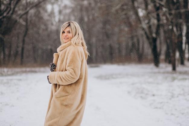Mooie vrouw in winterjas wandelen in park vol sneeuw Gratis Foto
