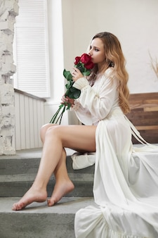 Mooie vrouw in wit ondergoed en neglige thuis in de badkamer. een verliefde vrouw rust uit