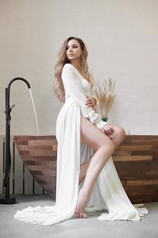 Mooie vrouw in wit ondergoed en negligé thuis in de badkamer