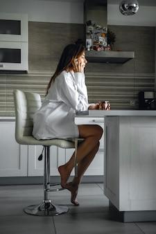 Mooie vrouw in wit overhemd zitten met een kopje thee in de keuken en praten op mobiele telefoon