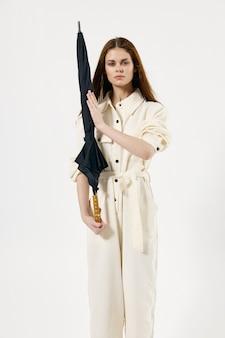 Mooie vrouw in wit pak met paraplu in het licht van de handenmanier