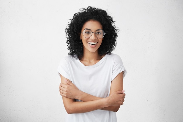 Mooie vrouw in wit t-shirt en ronde bril die verlegen voelt