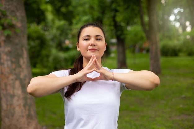 Mooie vrouw in wit t-shirt toont mudra in gevouwen vingers buiten