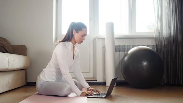 Mooie vrouw in wit trainingspak surft op internet met moderne laptop om nieuwe oefeningen te vinden op mat in de buurt van bank in lichte kamer afgezwakt