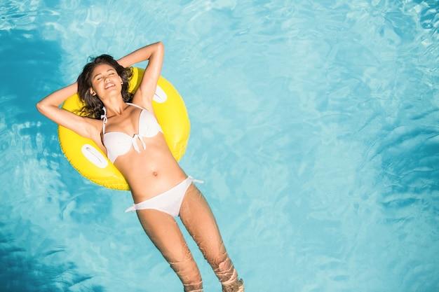 Mooie vrouw in witte bikini die op opblaasbare buis in zwembad drijft