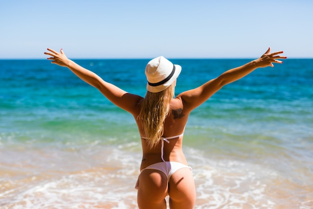 Mooie vrouw in witte bikini. jong en sportief meisje poseren op een strand in de zomer