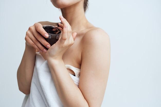 Mooie vrouw in witte handdoek naakte schouders zwarte crème in handen skin care spa procedure.