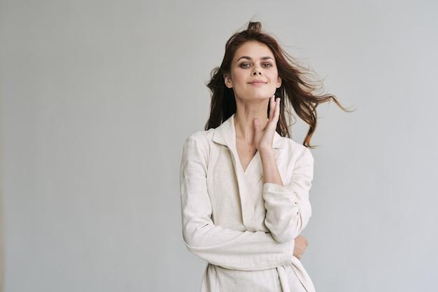 Mooie vrouw in witte jas glamour smile studio