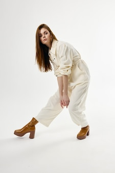 Mooie vrouw in witte jumpsuit leunde naar voren met bruine laarzen.