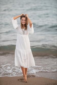 Mooie vrouw in witte jurk aan zee