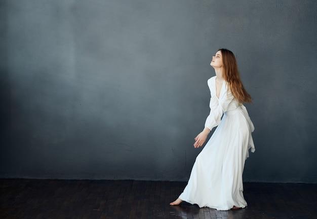 Mooie vrouw in witte jurk donkere achtergrond model